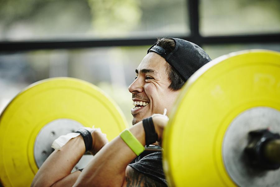 Smiling man preparing to press barbell over head Photograph by Thomas Barwick