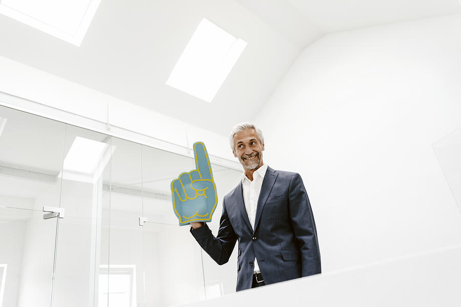 Smiling mature businessman holding toy hand in office Photograph by Westend61