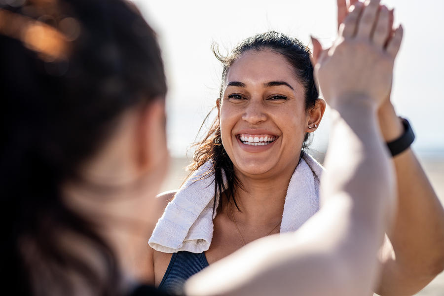 Smiling woman giving high five to her friend after exercising Photograph by Luis Alvarez