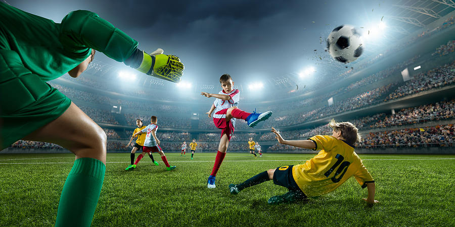 Soccer kids players scoring a goal. Goalkeeper tries to hit the ball Photograph by Aksonov