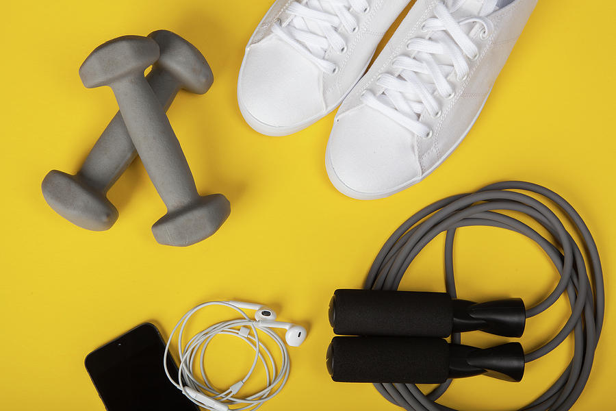 Sport Shoes, Dumbbells, Mobile Phone And Skipping Rope On Yellow Background. Top View. Fitness, Sport And Healthy Lifestyle Concept. Photograph