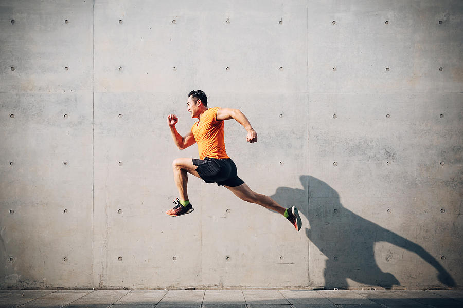 Sporty Asian Mid man running and jumping against shutter. Health and fitness concept. Photograph by Asia-Pacific Images Studio