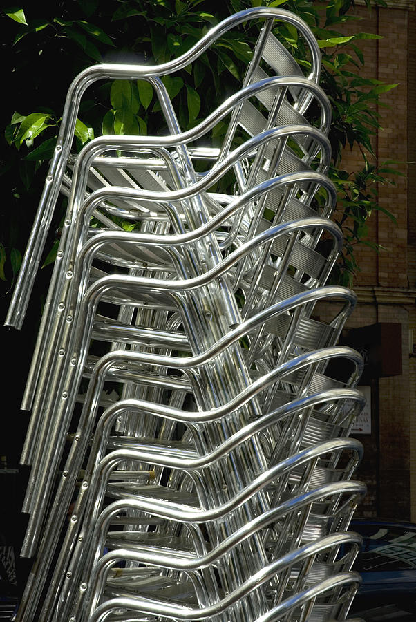 Stacked aluminium cafe chairs Photograph by Lyn Holly Coorg