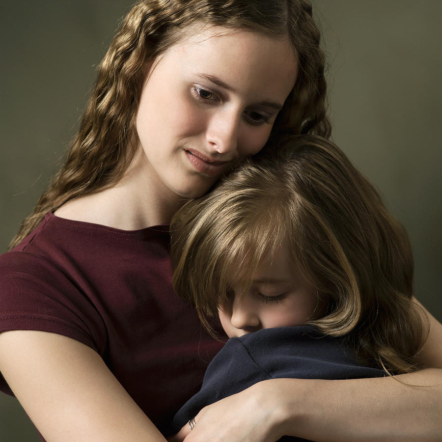 Studio Portrait Of A Caucasian Female Child With A Purple Shirt Hugging Her Little Sister Tightly Photograph by Photodisc