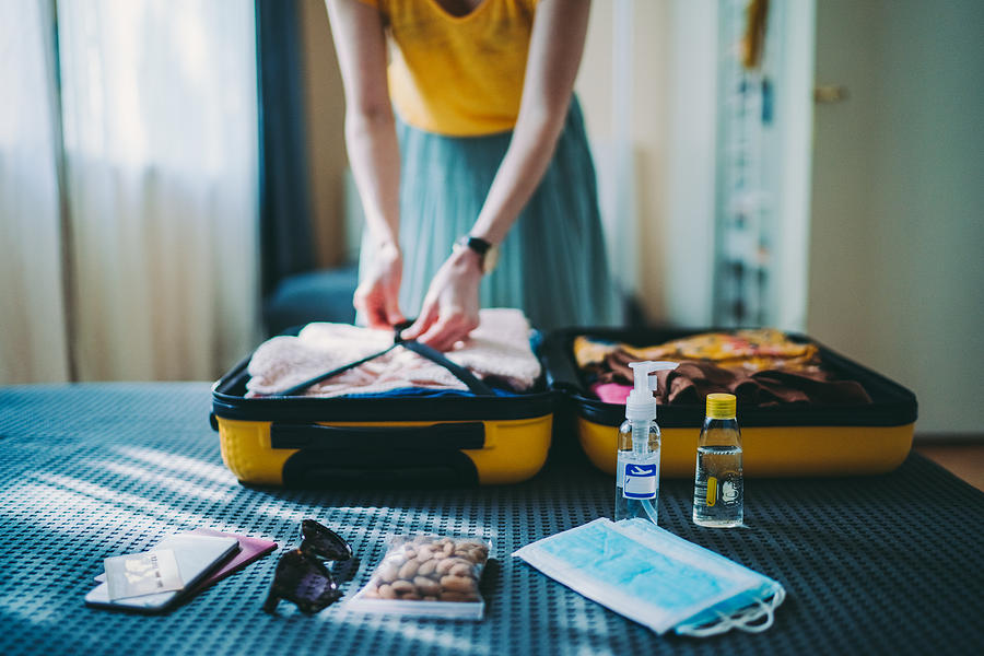 Suitcase packing for travel, COVID-19 Photograph by Martin-dm