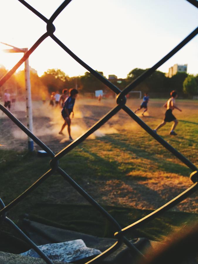Teenage kids playing soccer at sunset Photograph by Omid Scheybani / EyeEm