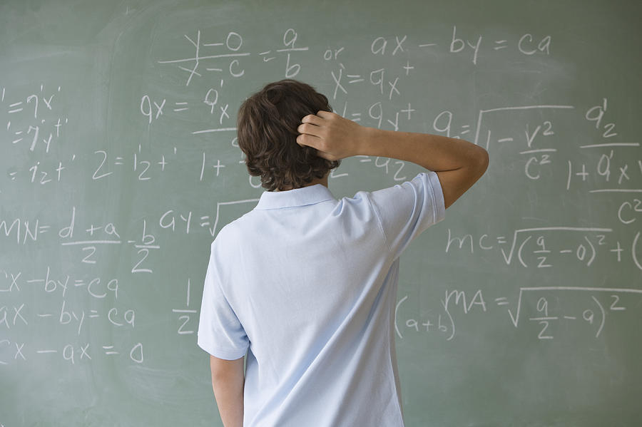Teenaged boy looking at math equations on blackboard Photograph by Tetra Images