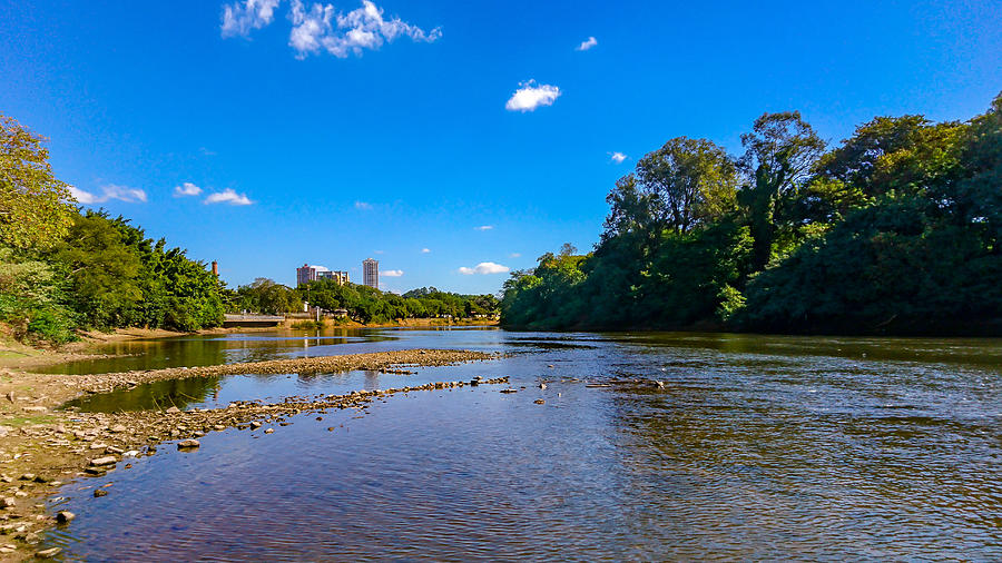 The Piracicaba River in a dry season, under blue sky between clouds. Photograph by CRMacedonio