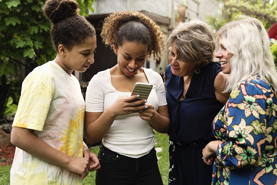 Three generation mixed-race family looking at mobile phone backyard. Photograph by Martinedoucet