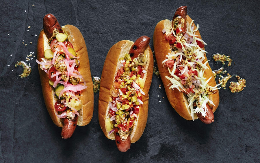 Three gourmet hot dogs on black background Photograph by Claudia Totir