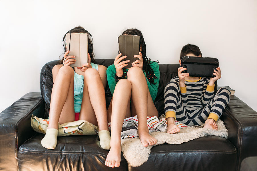Three Kids With Electronic Devices On A Sofa Photograph by Os Tartarouchos