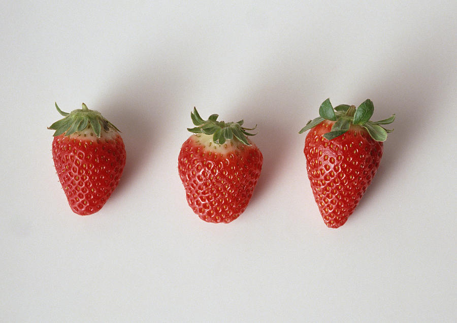 Three strawberries in a row, close-up, white background Photograph by Isabelle Rozenbaum & Frederic Cirou