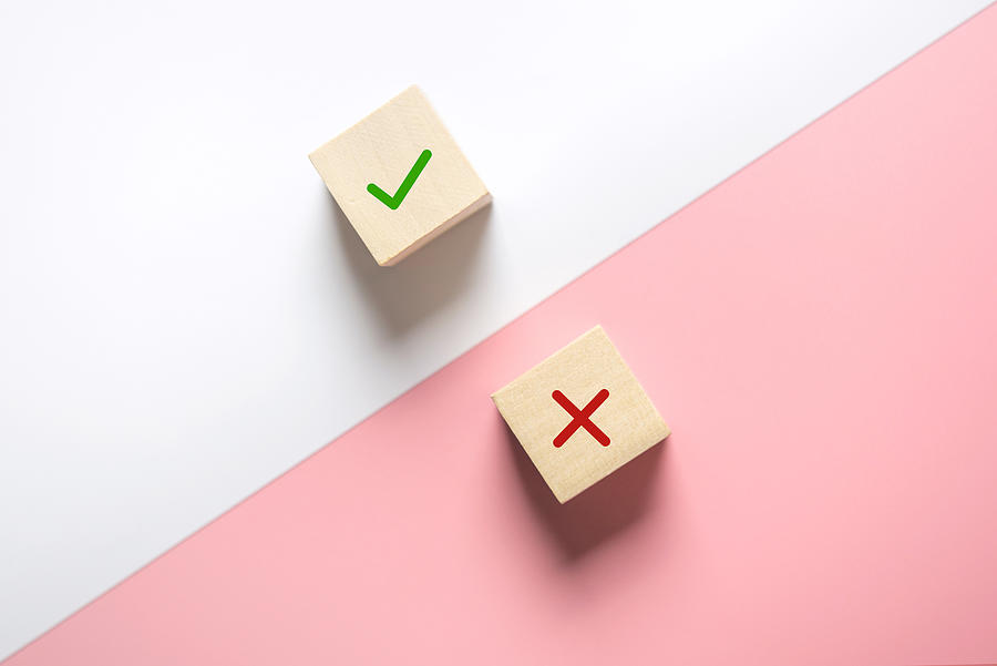 True and false symbols accept rejected for evaluation, Yes or No on wood blogs on pink and white background. Photograph by Oatawa