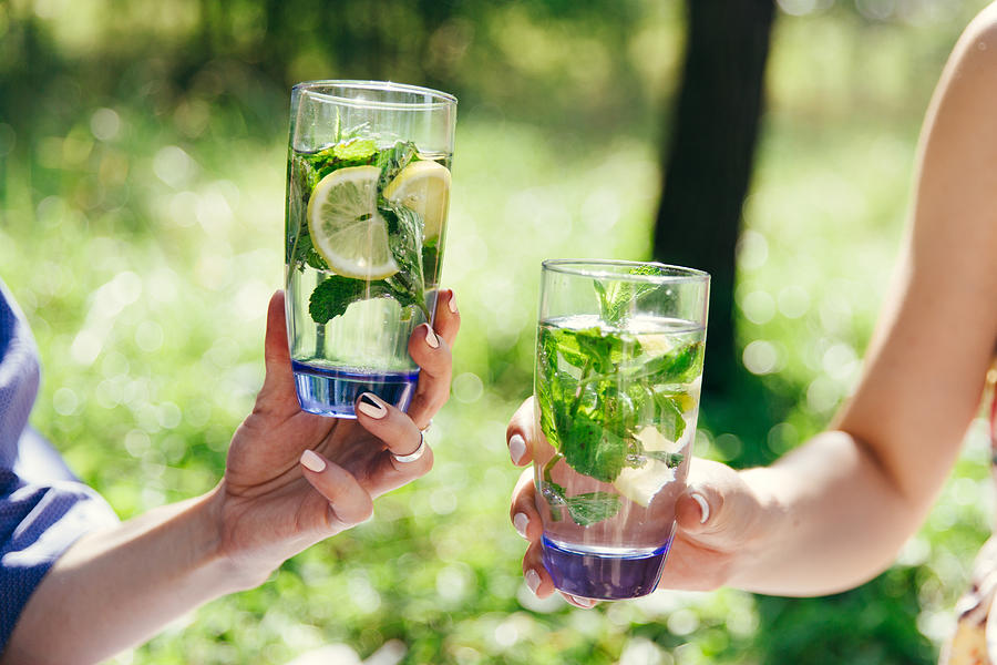 Two female hands holding glasses filled water with lemon and green mint leaves. Picnic in the garden. Detox, healthy eating, drinks, diet and people concept. Summer, outdoors. Photograph by Drawndream