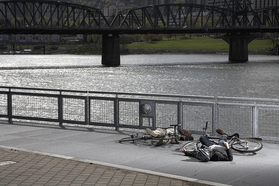 Two men with bicycles lying on pavement by river after collision Photograph by Kim Carson