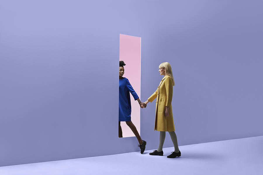 Two women holding hands, walking threw rectangular opening in coloured wall Photograph by Klaus Vedfelt