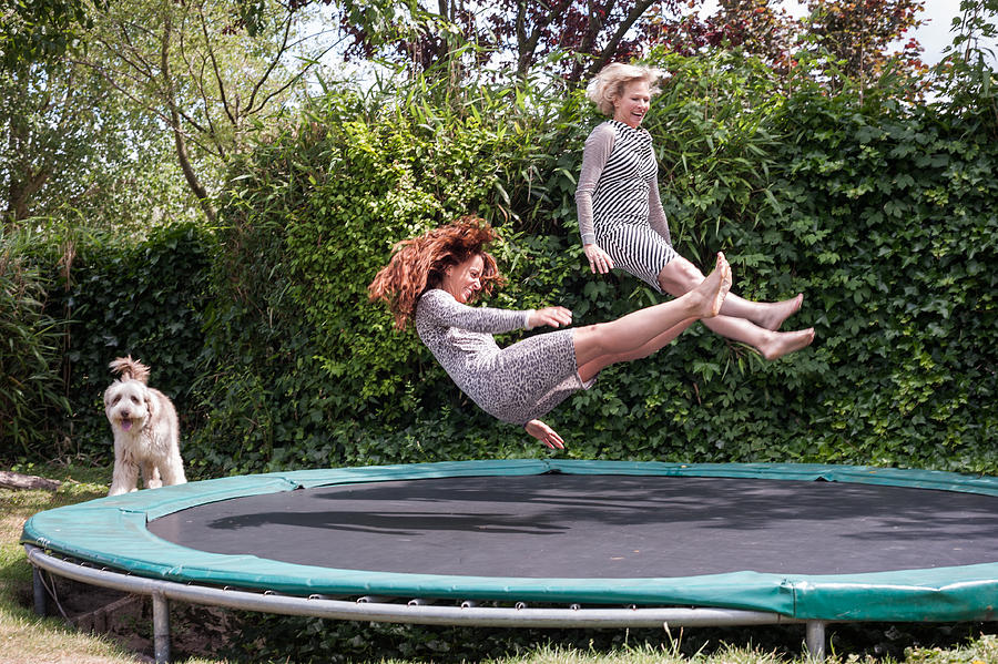 Two women playing on trampoline Photograph by Lucy Lambriex