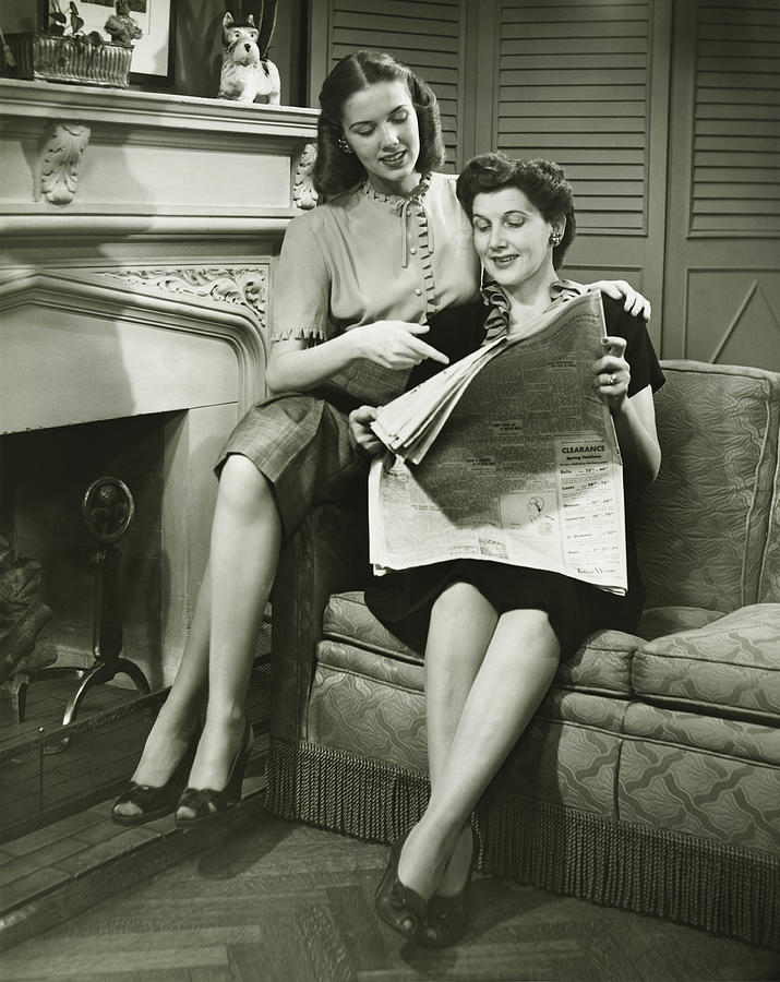 Two women sitting by fireplace, reading newspaper, (B&W) Photograph by George Marks