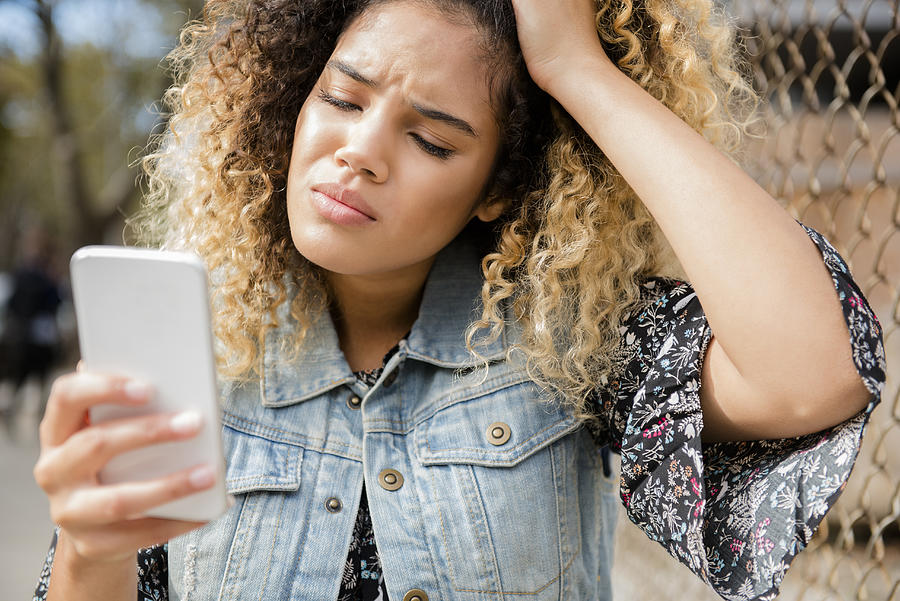 Unhappy Mixed Race woman texting on cell phone Photograph by JGI/Jamie Grill