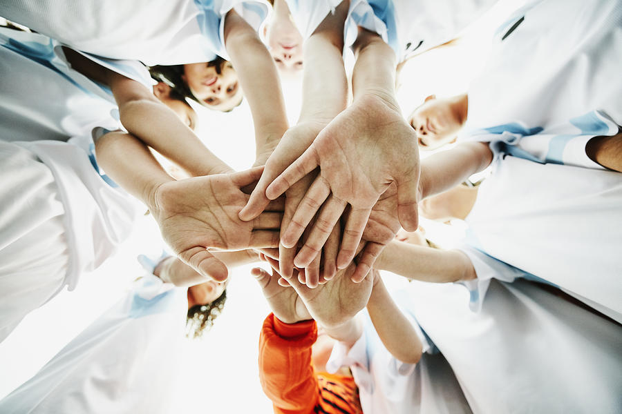 View from below of young female soccer players bringing hands together before game Photograph by Thomas Barwick