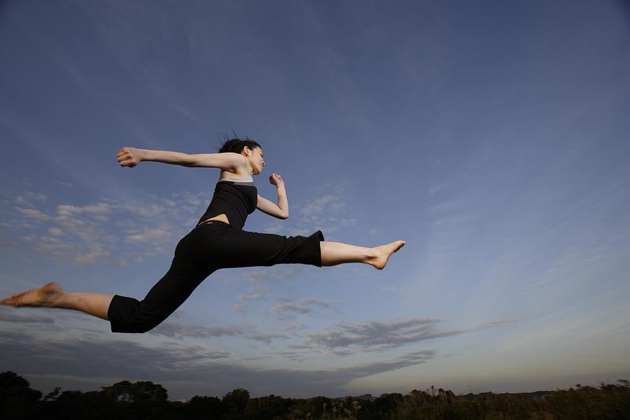 View of a young woman jumping in the air Photograph by imagewerks RF