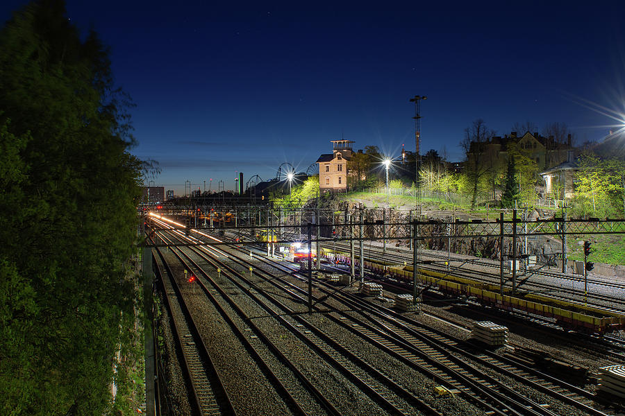 Night Photograph - Watching over the railtracks by Marko Hannula