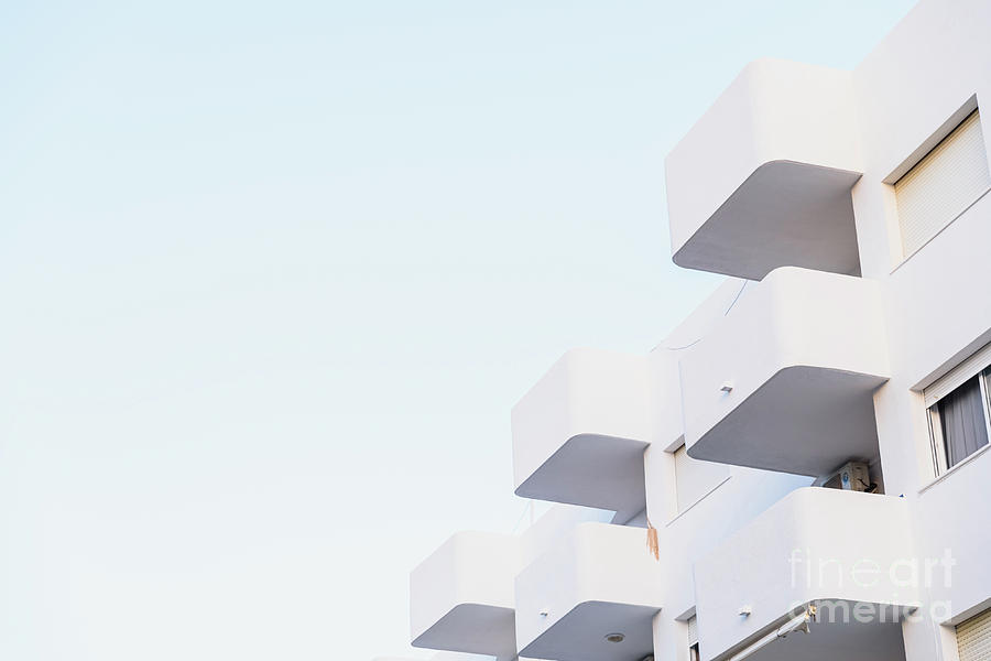 White buildings of round terraces in minimalist style near the sea. by Joaquin Corbalan