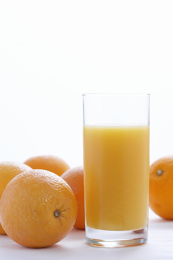 Whole oranges by orange juice in glass, close-up Photograph by Martin Poole