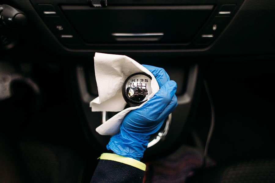 Wiping down gear shift lever in a car Photograph by Os Tartarouchos