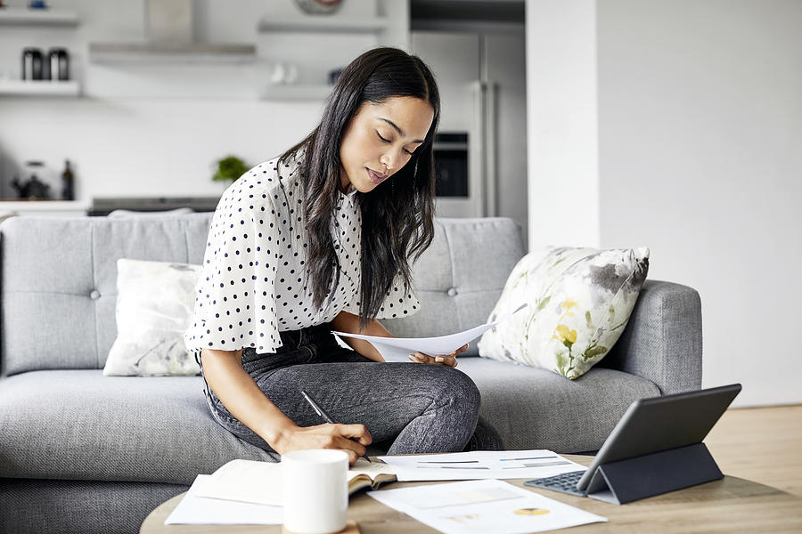 Woman analyzing documents while sitting at home Photograph by Morsa Images