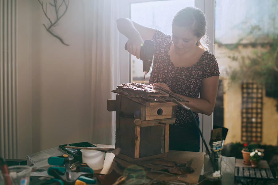 Woman building a bird house. Photograph by Guido Mieth