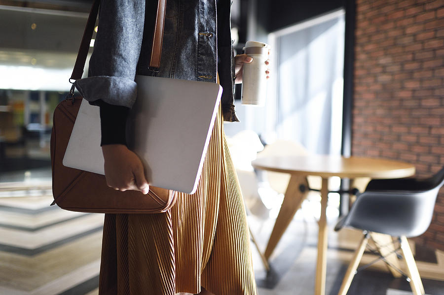 Woman carrying laptop, purse and reusable coffee cup to work Photograph by Carlina Teteris