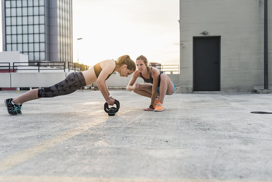 Woman cheering at training partner kettlebell on parking level in the city Photograph by Westend61