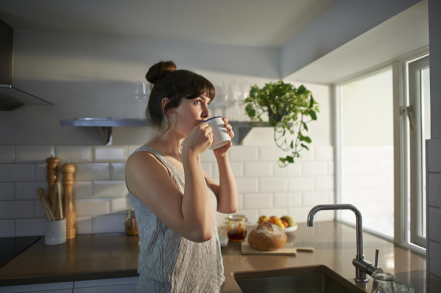 Woman drinking from mug in zero waste kitchen. Photograph by Dougal Waters