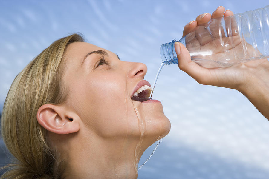 Woman drinking water Photograph by Jupiterimages