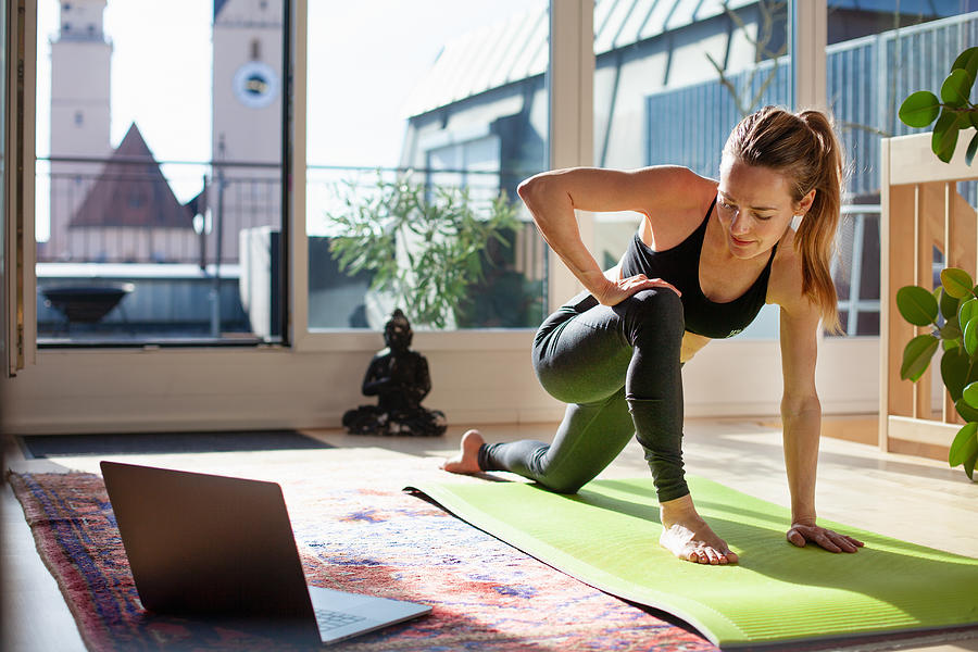 Woman exercising at home in front of her laptop, stretching her legs Photograph by Kathrin Ziegler