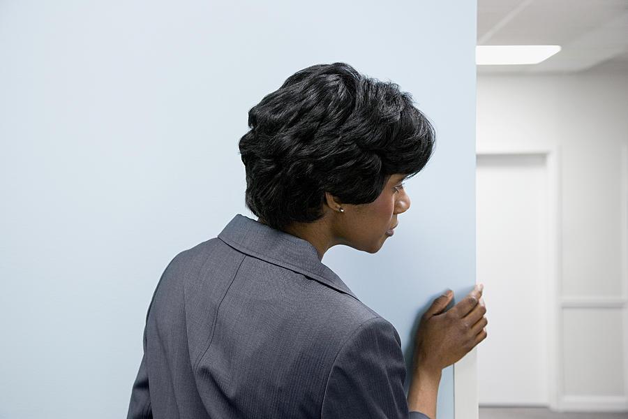 Woman hiding peering round corner Photograph by XiXinXing