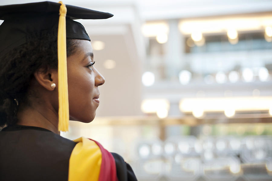 Woman in graduation gown looking away Photograph by Cavan Images