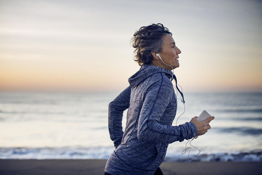 Woman jogging while listening music at beach against sky Photograph by Cavan Images