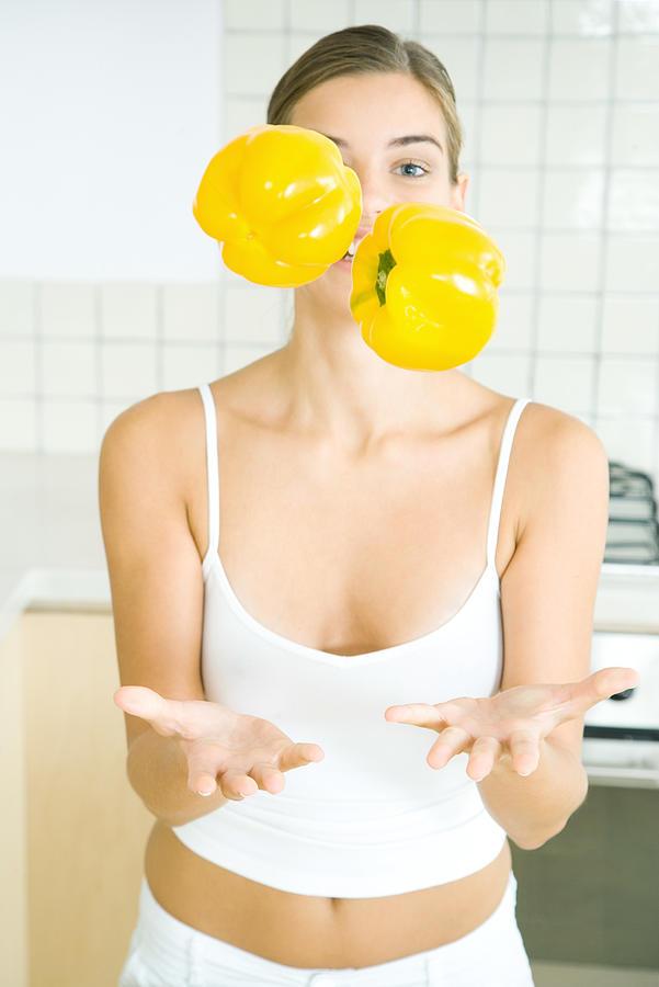 Woman juggling yellow bell peppers in kitchen Photograph by PhotoAlto/Rafal Strzechowski