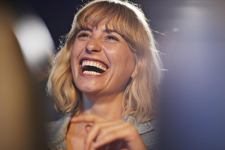 Woman laughing during comedy movie Photograph by Klaus Vedfelt