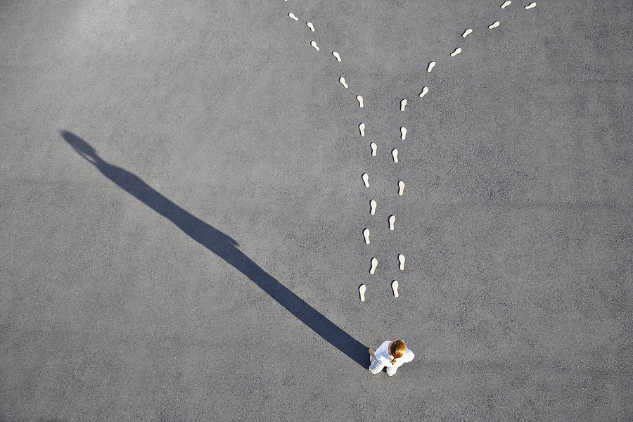 Woman looking at diverging footprints Photograph by Martin Barraud