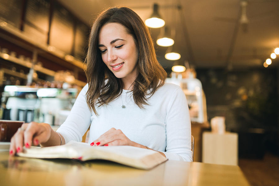 Woman Reading Book in Coffee Shop Photograph by RyanJLane
