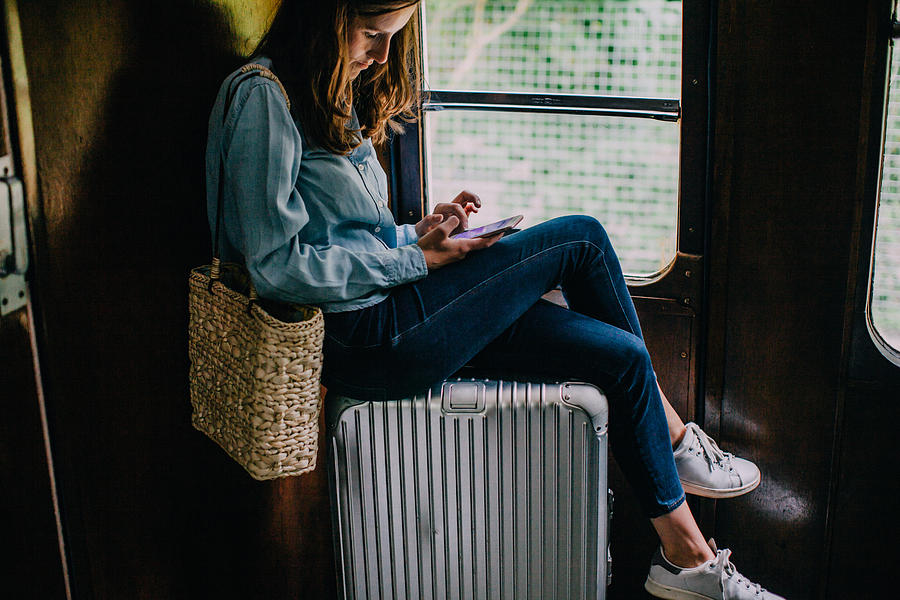 Woman sitting on suitcase in train looking at smart phone Photograph by Counter