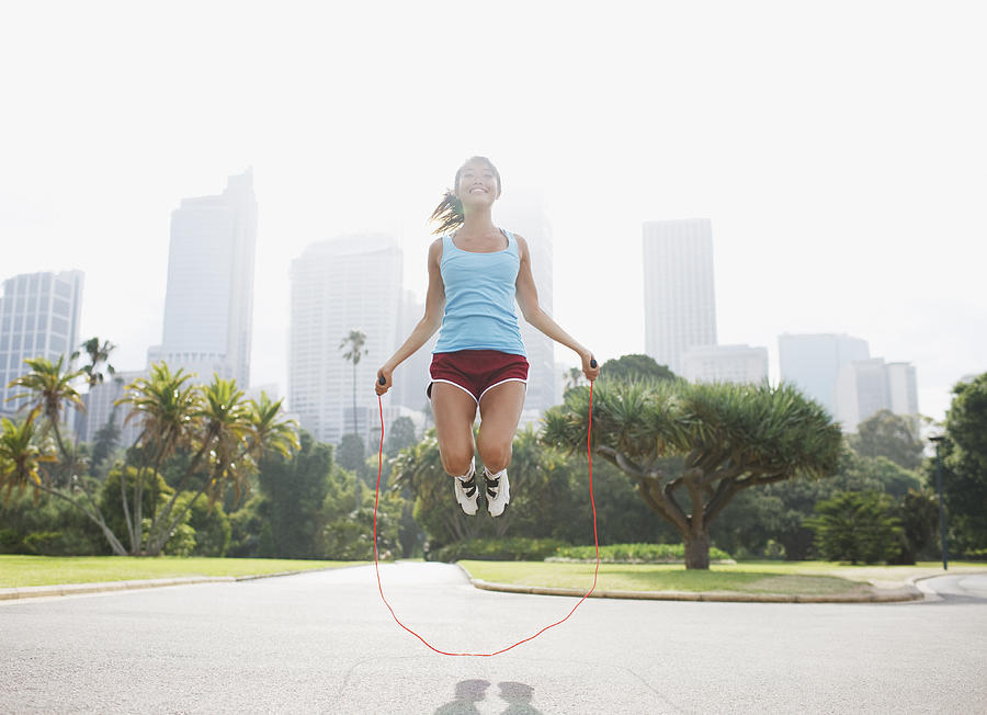 Woman skipping rope in park Photograph by Tom Merton