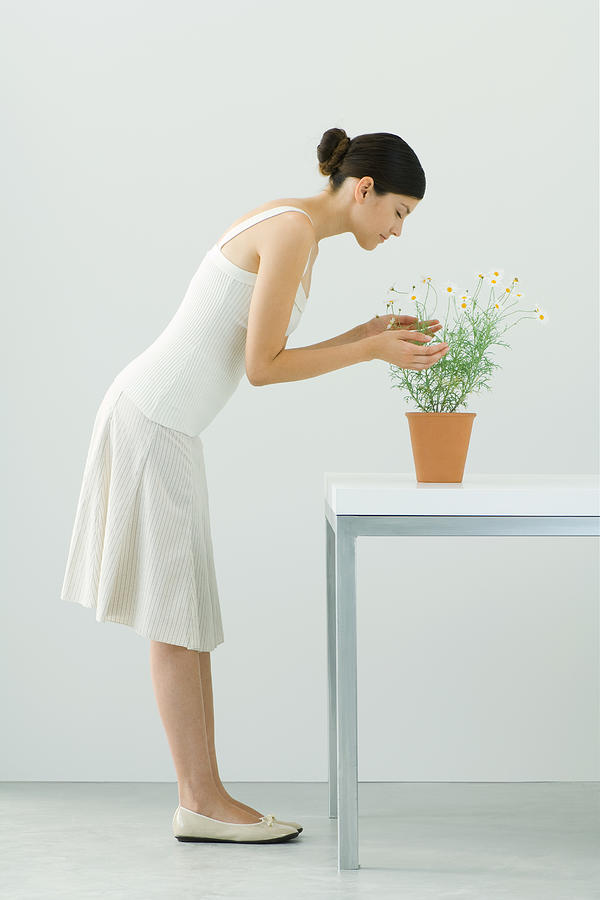 Woman smelling potted chamomile plant, eyes closed, side view Photograph by ZenShui/Milena Boniek