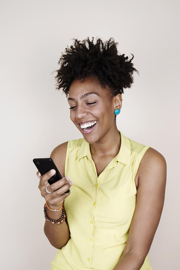 Woman smiling using phone Photograph by Flashpop