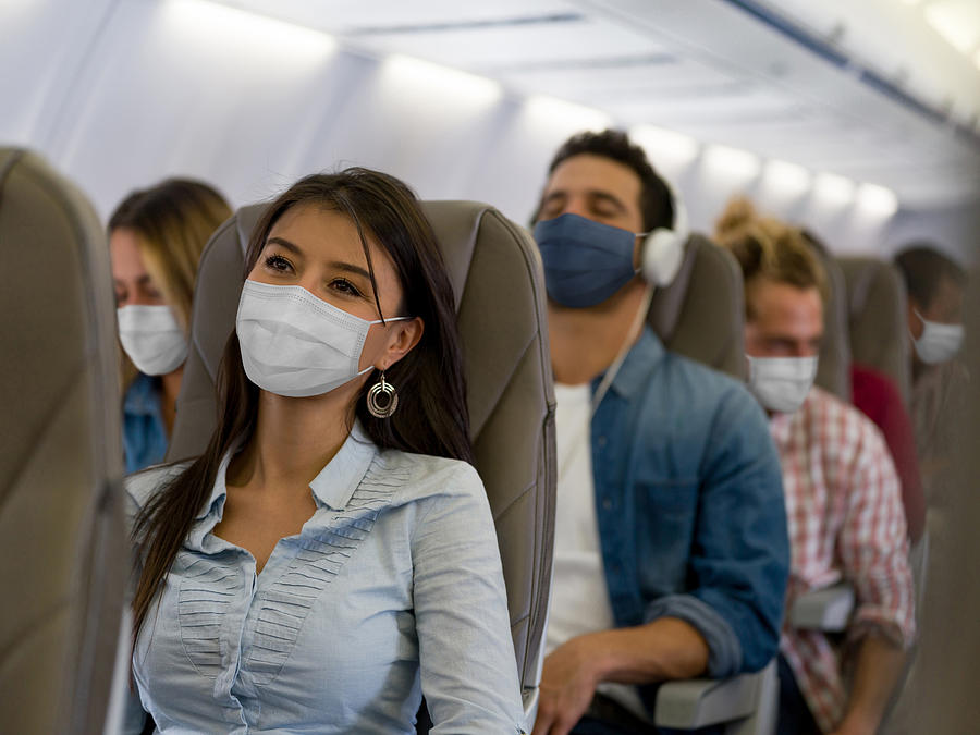 Woman traveling by plane wearing a facemask Photograph by Hispanolistic