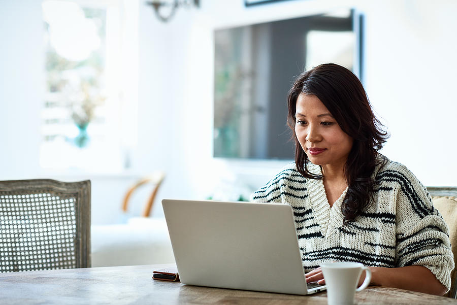 Woman using laptop and working from home Photograph by 10000 Hours