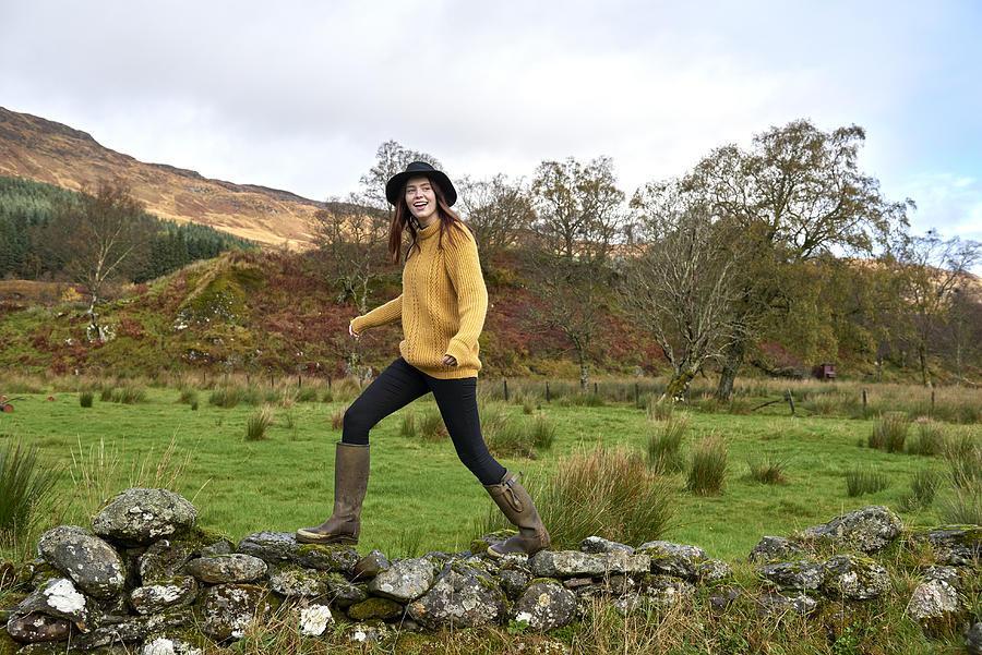 Woman walking along stone wall Photograph by Plume Creative